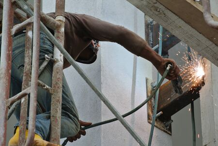 Welders taking very high risk working at high level at the construction site.