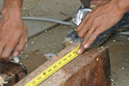 erecting: Workers using measuring tape to measure mild steel at the construction site Stock Photo