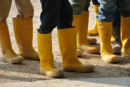 Construction workers in boots at the construction site. Standard-Bild