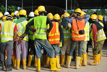 Group of construction workers assemble at the open space in the construction site.
