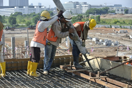 concrete pump: Construction workers are doing the concrete work using hose from the elephant crane or concrete pump crane on May 15, 2014 at Sepang, Malaysia. Editorial