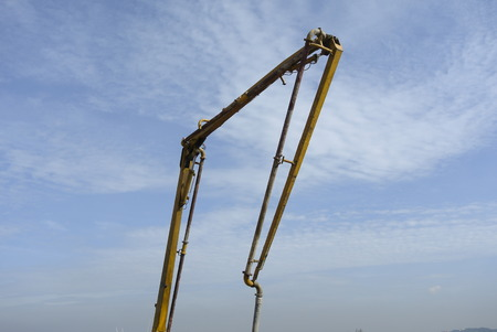 concreting: Construction workers using concrete pump crane with high pressure pump to move concrete from a concrete truck to the concreting site.