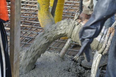 Construction workers are doing the concrete work using hose from the elephant crane or concrete pump crane on May 15, 2014 at Sepang, Malaysia. Sajtókép
