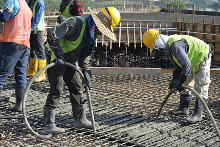 compacting: Construction workers using a concrete vibrator at a construction site in Selangor, Malaysia. Concrete vibrator is used for compacting new concrete was cast.
