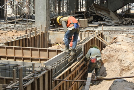 formwork: Two Construction Workers Installing Ground Beam Formwork