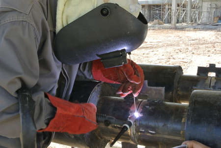 A licensed welders welding pipe. He is hired to do welding work on the pipeline. Stock Photo