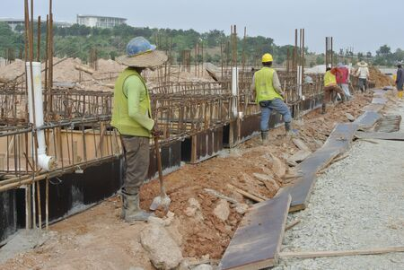 formwork: Group of construction workers are working at ground beam formwork. Formwork is installed on the ground before any work is carried out to install the steel reinforcements bar.