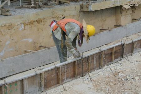 to proceed: A construction workers are installing ground beam formwork. Formwork is installed on the ground before proceed with concrete casting work.