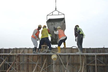 formwork: A group of construction workers pouring concrete using concrete bucket into the timber formwork. Stock Photo