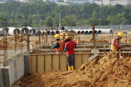 proceed: Group of construction workers installing ground beam formwork. Formwork is installed on the ground before proceed with concrete casting work. Editorial