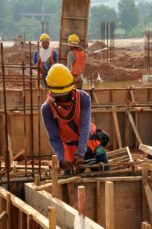 formwork: A carpenter working at construction site preparing timber formwork.