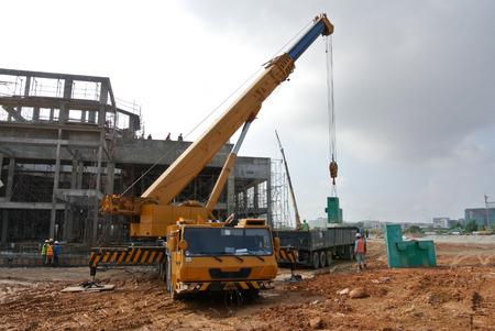 移動式クレーンは、建設現場で重量物を持ち上げるための重いマシンです。 写真素材