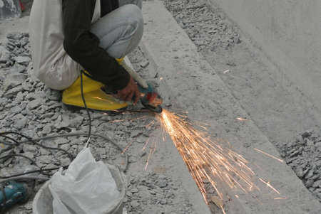 grind: Construction workers using grinder to grind metal surface at the construction site