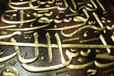 merbau: Quran words made from traditional wood carving and finish with gold. Stock Photo