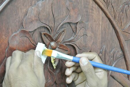 graver: Skilled craftman adding gold leaf skin to the Malaysian traditional woof carving.