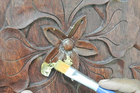 merbau: Skilled craftman adding gold leaf skin to the Malaysian traditional woof carving.