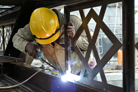 Welders welded the decorative mild steel at the construction site photo