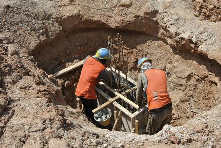 formwork: Construction workers installing the pile cap formwork at the construction site.