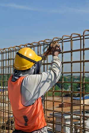 fabricate: Construction worker fabricate retaining wall reinforcement bar at the construction site. Stock Photo