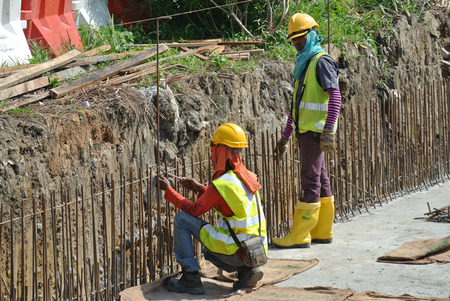 fabricate: SELANGOR, MALAYSIA  FEBRUARY, 2015: Construction workers fabricate retaining wall reinforcement bar at the construction site. Editorial