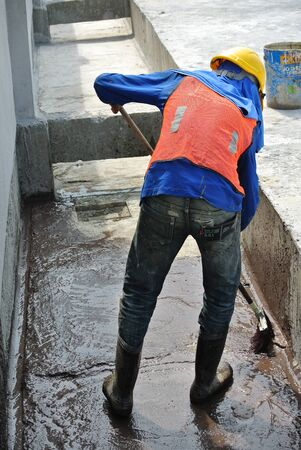 waterproofing: A construction worker apply layer of bituminous waterproofing at the building roof slab surface.