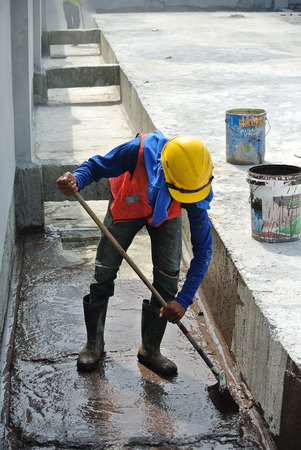 penetration: A construction worker apply layer of bituminous waterproofing at the building roof slab surface.