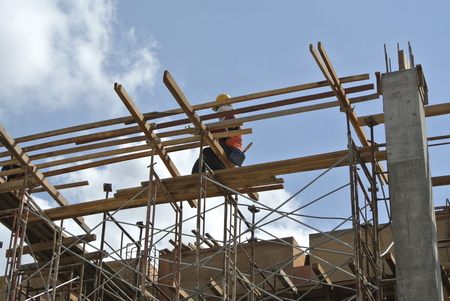fabricating: A construction worker fabricating building timber beam formwork. Workers stand on a temporary structure which is supported by scaffolding. Stock Photo