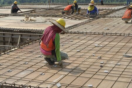 formwork: Group of construction workers fabricating floor slab reinforcement bar and formwork Stock Photo