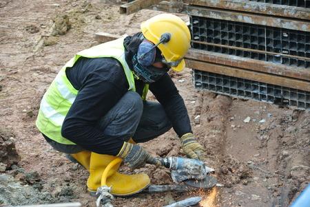 sharpen: A construction worker using construction grinder to sharpen steel at the construction site