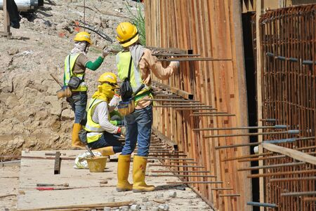 Construction workers fabricate retaining wall reinforcement bar and formwork at the construction site in Selangor, Malaysia on April 10, 2015. .