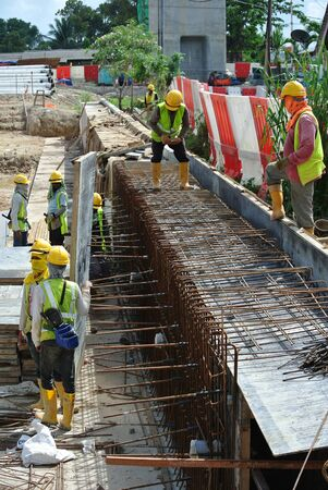 fabricate: Construction workers fabricate retaining wall reinforcement bar and formwork at the construction site in Selangor, Malaysia on April 10, 2015. .