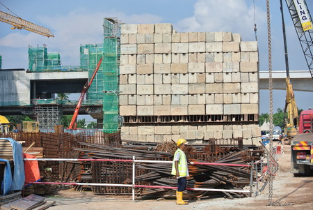 uplift: Construction workers stacking the maintain load test block at the construction site in Selangor, Malaysia on May 25, 2015. The block used to test the piling integrity. Editorial