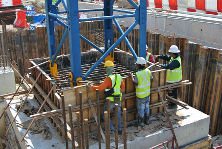 timber: MELAKA, MALAYSIA  AUGUST 20, 2015: Group of construction workers fabricating column stumb formwork at the construction site. The formwork was made from timber and plywood.