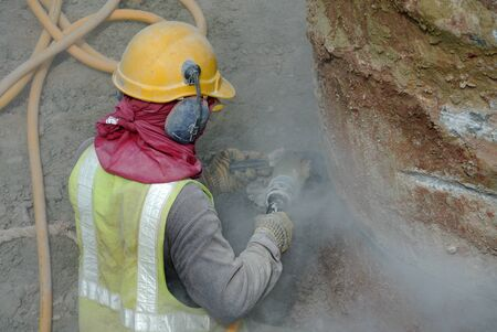 noise pollution: SELANGOR, MALAYSIA  MAY, 2015: A construction worker using construction grinder to cut concrete pile at the conctruction site.