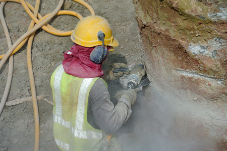 ruido: Selangor, Malaysia MAYO, 2015: Un trabajador de la construcción que usa la amoladora de construcción para cortar pila de concreto en el sitio conctruction. Editorial
