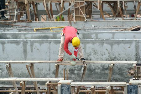 fabricating: SELANGOR, MALAYSIA  NOVEMBER 25, 2014: A construction worker fabricating building timber beam formwork at the construction site. Workers stand on a temporary structure which is supported by scaffolding.