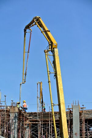 Construction workers using concrete pump crane with high pressure pump to move concrete from a concrete truck to the concreting site Standard-Bild