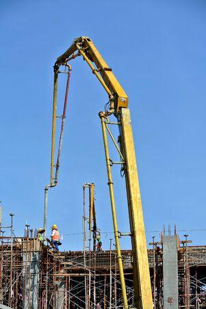 concrete pump: Construction workers using concrete pump crane with high pressure pump to move concrete from a concrete truck to the concreting site Stock Photo