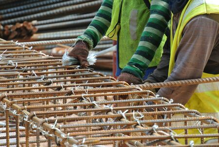 fabricating: Group of construction workers fabricating pile cap steel reinforcement bar at the construction site. Stock Photo
