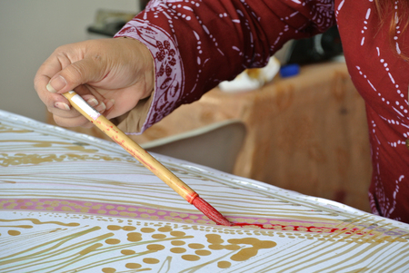 white cloth: A lady doing Malaysian traditional batik tulis using hot wax on piece of white cloth.