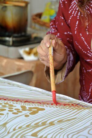 흰색 천으로 조각에 뜨거운 왁 스를 사용 하여 말레이시아 전통 바 틱 tulis 하 고 숙 녀.