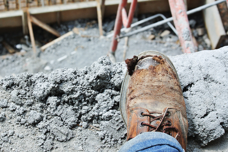 safety boots: SELANGOR, MALAYSIA  AUGUST 28, 2014: Old safety boots against a background of a construction site