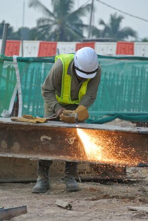blowtorch: Construction worker cutting metal using blowtorch at the construction site