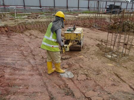 compaction: JOHOR, MALAYSIA  SEPTEMBER 25, 2014: Construction workers using baby roller compactor to compact soil at the construction site in Johor, Malaysia on September 15, 2014. Editorial