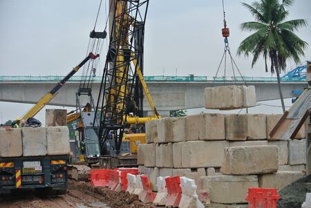 uplift: SELANGOR, MALAYSIA  APRIL 08, 2015: Construction workers stacking the maintain load test block at the construction site in Selangor, Malaysia. The block used to test the piling integrity.