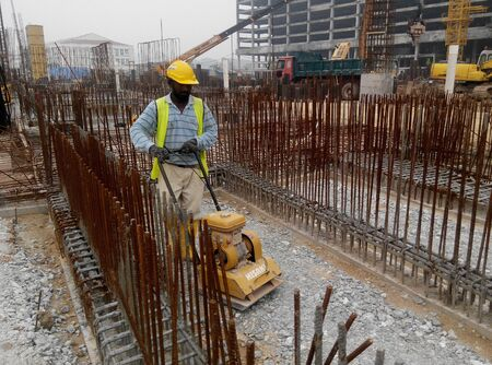 compaction: SELANGOR, MALAYSIA  SEPTEMBER 11, 2014: Builder worker at sand ground compaction with vibration plate compactor machine at construction site on September 11, 2015 before placing slab reinforcement bar stage.