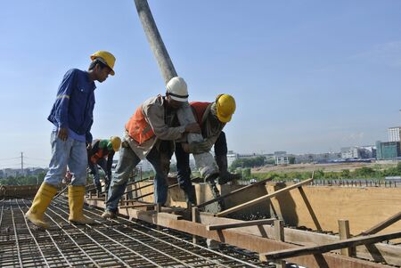concreting: Construction workers are doing the concreting work using hose from the elephant crane or concrete pump crane at the construction site in Selangor, Malaysia