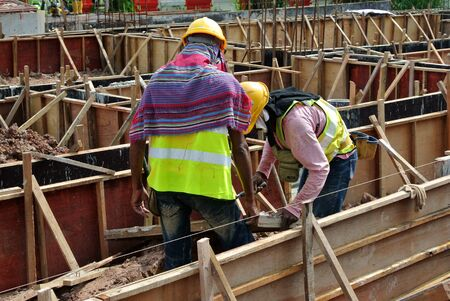 fabricating: JOHOR, MALAYSIA  AUGUST 21, 2015: A construction workers fabricating ground beam formwork at the construction site in Johor, Malaysia on August 21, 2015.