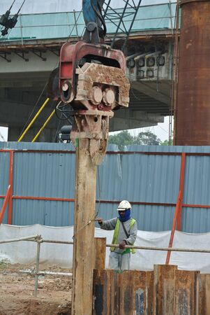 sheet pile: MALACCA, MALAYSIA  SEPTEMBER 15, 2015: Retaining wall steel sheet pile cofferdam. Driving machine at work in construction site. Sheet pile driven machine driven the pile to the earth using vibrated hydraulic arm. Workers control. Editorial