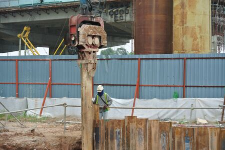 driven: MALACCA, MALAYSIA  SEPTEMBER 15, 2015: Retaining wall steel sheet pile cofferdam. Driving machine at work in construction site. Sheet pile driven machine driven the pile to the earth using vibrated hydraulic arm. Workers control. Editorial